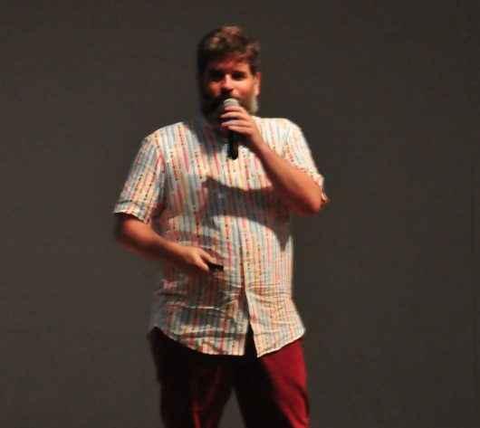Edgar está no palco do Teatro Mario Covas. Ele veste calça vermelha de brim, blusa de tecido bege de manga curta e sapatos pretos.
