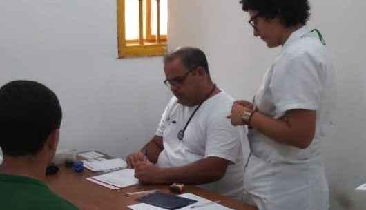Médico e enfermeira em sala realizam consulta a um jovem rapaz